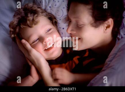 Mother and son embracing in bed