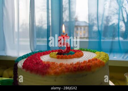 Birthday - anniversary colorful cake with lit red candle showing nr. 5 - Stock Photo