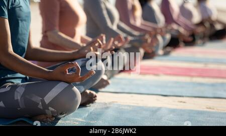 Side view of women aligned doing yoga together - Stock Photo