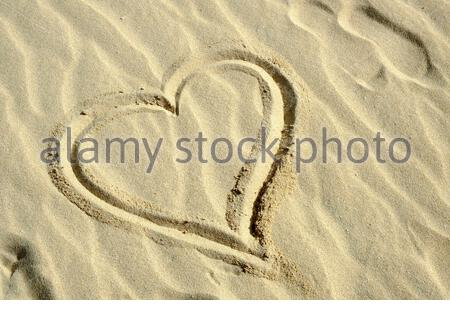 Love heart drawn in the sand - Stock Photo