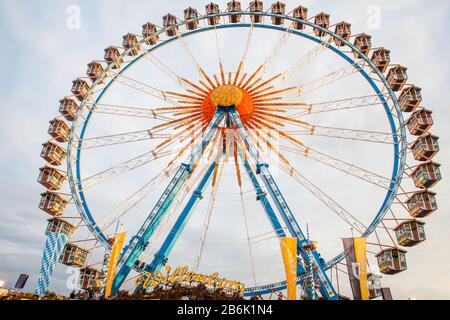 The Willenborg ferris-wheel rises up, high above the Oktoberfest celebration in Theresienwiese, Munich. In between beer and food, attendees take rides. - Stock Photo