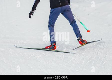 Close-up of cross country skiing equipment - boots and poles on a snow background - Stock Photo