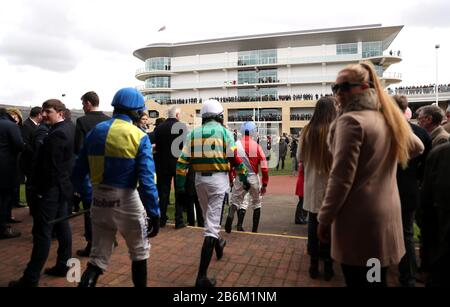 Jockeys walk out ahead of the first race during day two of the Cheltenham Festival at Cheltenham Racecourse. - Stock Photo
