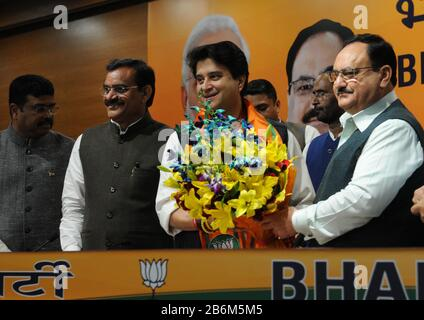 India. 11th Mar, 2020. Former senior Congress party leader, Jyotiraditya Scindia, center, receives a bouquet from Bharatiya Janata Party president Jagat Prakash Nadda during a press conference as he joins the BJP a day after quitting Congress in New Delhi, India (Photo by Sondeep Shankar/Pacific Press) Credit: Pacific Press Agency/Alamy Live News - Stock Photo