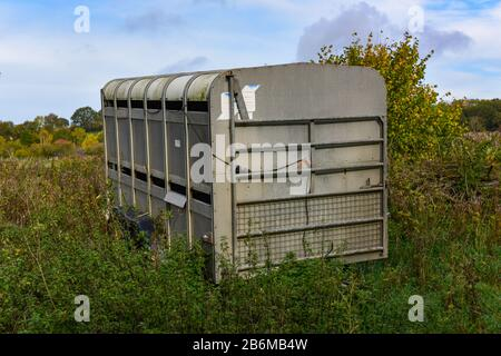 Unused stock trailer in a field with shrubs and weeds growing up around it. - Stock Photo