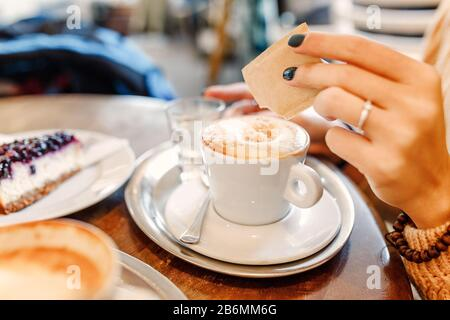 a woman pours sugar into a mug of cappuccino in cafe