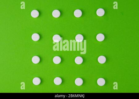 white pills laid out in the shape of a square on a green background. copy space for text - Stock Photo