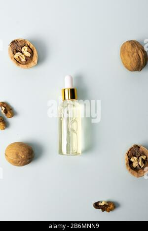 Cosmetic and medicinal oil of walnut on blue pastel background. Walnut cosmetic moisturizing serum. The concept of natural ingredients in cosmetics. - Stock Photo