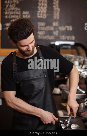 Young male barista pressing ground coffee into bottomless portafilter holder using tamper. Preparing espresso in professional coffee machine. Brewing - Stock Photo