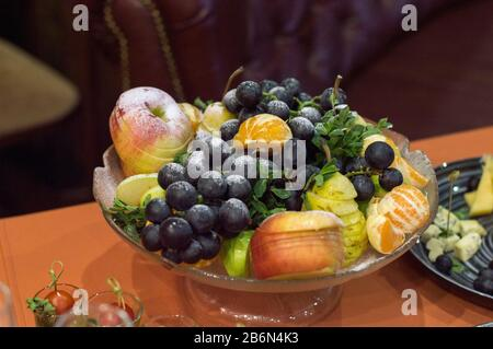 Vase with fruits on the table. Sliced and cooked for dinner.