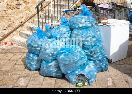 garbage in plastic blue bags on the street of the Eastern city. in blue bags plastic bottles - Stock Photo