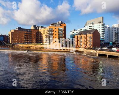 Modern apartment buildings by the River Aire in spate due to recent rain storms Leeds West Yorkshire England