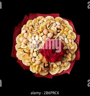 Large bouquet consisting of exotic dried fruits and nuts, decorated with a large red rose on black background, top view. - Stock Photo