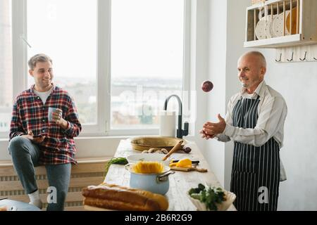 Young man and his father cooking in kitchen - Stock Photo