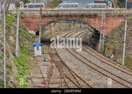 Istanbul, Turkey - February 11, 2020: Rusty railroad rails and an old stone automobile bridge over them. - Stock Photo
