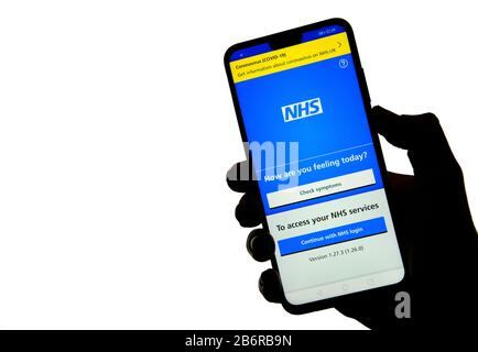 Stone / United Kingdom - March 11 2020: NHS app on the silhouette of a smartphone hold in hand. - Stock Photo