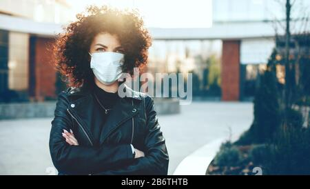 Caucasian woman posing with crossed hands while wearing an anti flu mask and looking at camera - Stock Photo