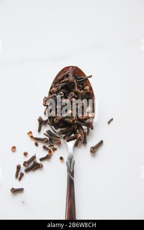 Dried cloves in spoon on grey marble background. Spice for hot tea, winter drinks and food. Close up and top view