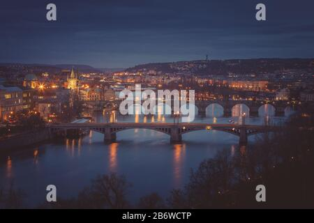 Moody evening in Prague. Seven bridges on Vltava river view from Letna Hill. Scenic panorama of old, medival city with arched bridges over the Vltava Stock Photo