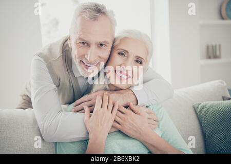 Close up photo of lovely bonding people enjoying wearing shirt teal pullover sit divan in light room house indoors - Stock Photo