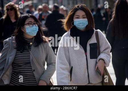 Barcelona, Spain. 12th March 2020 - Women wearing protective face masks walk La Rambla in Barcelona. President Donald Trump announced  restrictions on travelling  from  Europe to the United States due  coronavirus pandemic. Credit:Jordi Boixareu/Alamy Live News - Stock Photo