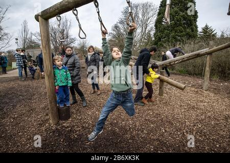 Active boys climbing on the RHS Back to Nature Garden outdoor activity area at RHS Wisley co-designed by The Duchess of Cambridge, Surrey, England, UK - Stock Photo