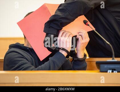 12 March 2020, Lower Saxony, Hanover: The defendant's handcuffs are taken off shortly before the start of the trial. Prelude in the trial against a 33-year-old man from Morocco for the murder of a 61-year-old woman in Hanover The defendant is accused of having attacked the 61-year-old woman, whom he had met in the context of refugee aid, in her attic apartment and having tied her up in a cruel way in order to obtain her gold coins and jewellery with a total value of almost 100,000 euros. The victim suffocated in agony because the perpetrator had completely wrapped her head in adhesive tape. Ph