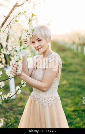 Portrait of young blond Caucasian woman in elegant dress posing in the flowered garden in the spring time. Young beautiful bride in blooming garden. - Stock Photo