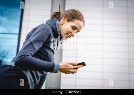 Junge, sportliche Frau macht während des Joggens eine Pause mit Handy in der Hand.  Young, sporty woman takes a break with a cell phone in her hand. Stock Photo