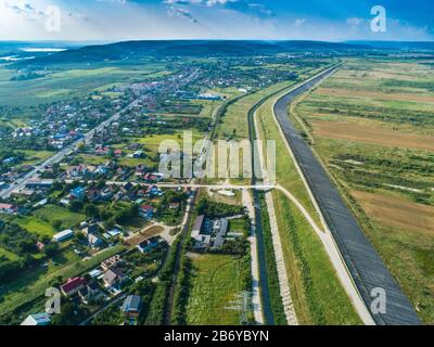 Drone view of dam wall near residential area with forest in the background - Stock Photo