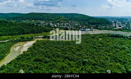 Drone view of a river crossing a beautiful forest landscape inside a dam with small town in the background - Stock Photo