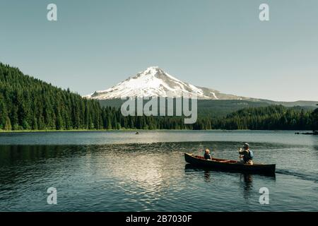 A father canoes with his daughter on Trillium Lake near Mt. Hood, OR. - Stock Photo