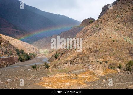 Morocco, Marrakesh-Safi (Marrakesh-Tensift-El Haouz), Al Haouz Province. Rainbow in a gorge, Tizi N'Tichka pass in the Atlas Mountains. - Stock Photo