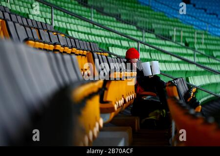 A general view of one fan surrounded by empty seats ahead of the UEFA Europa League round of 16 first leg match at Linzer Stadion, Linz. - Stock Photo