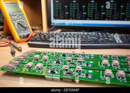 Set of resistors on semiconductor plate, on table is a radio technician in front of computer and multimeter - Stock Photo