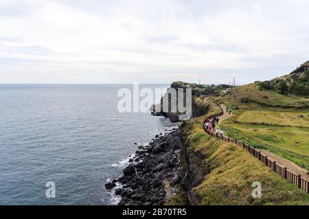People Walking along the High Cliff Coast. No 10 Course in Songaksan On Jeju island, Korea. - Stock Photo