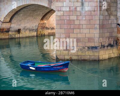 Small rowing boat in front of the La Barquera Bridge in the harbor of San Vicente de la Barquera, Cantabria, Spain - Stock Photo