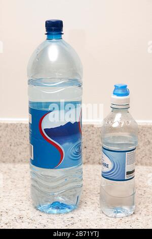 large and small plastic bottles of spring water - Stock Photo