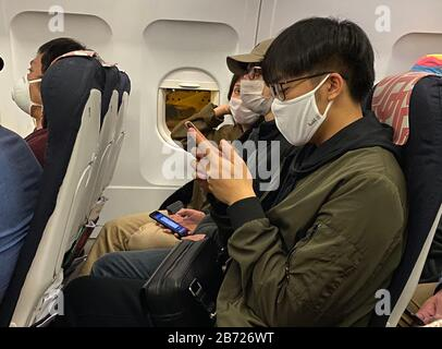Lisbon, Portugal. 12th Mar, 2020. Passengers flying at 5:30 a.m. from Humberto Delgado Airport in Lisbon, Portugal to Paris March 12, 2020 wear masks because of the Coronavirus pandemic. Credit: Mark Hertzberg/ZUMA Wire/Alamy Live News - Stock Photo