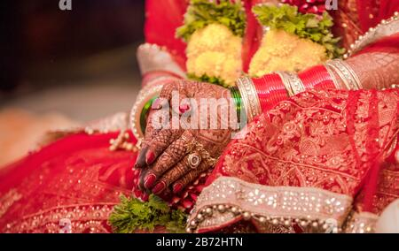 Beautiful photo of Indian bride in traditional wedding of Hindu custom wearing colorful bangles and sitting with folded hands in her marriage ceremony - Stock Photo
