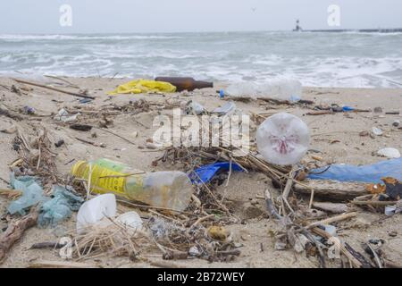 Spilled garbage on the beach of the big city. Empty used dirty plastic bottles, bags and other rubbish on the seashore. Stock Photo