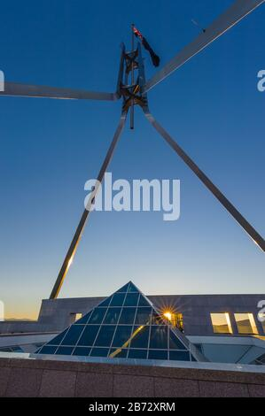 View of the roof top flagpole and glass pyramid skylight on the New Parliament House in Canberra. - Stock Photo