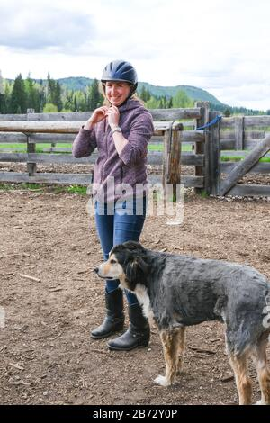 A young woman with a dog getting ready to go horse riding in Banff national park. - Stock Photo