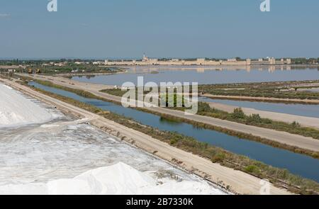 Aigues-Mortes, Salins du Midi, panorama with pink lake and Aigues-Mortes in background, France. - Stock Photo