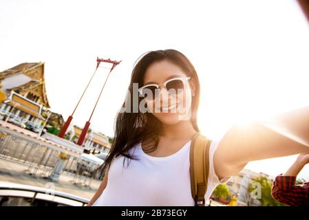 Smiling young beautiful Asian woman wearing sunglasses taking a selfie at the Giant Swing while travelling in Bangkok Thailand - Stock Photo