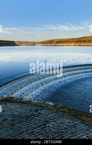 Water flowing over spillway from calm scenic tree-lined lake, under deep blue sky - Fewston Reservoir, Washburn Valley, North Yorkshire, England, UK.