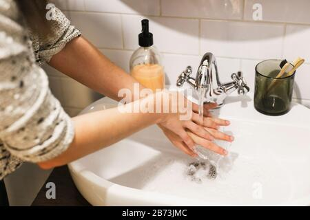 Washing hands. Hands washing under flowing water with proper technique and antibacterial soap in bathroom. Prevent coronavirus epidemic. Prevention of