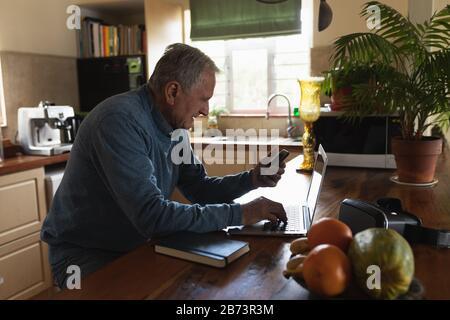 Senior man using laptop in his kitchen