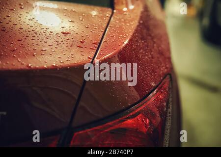 close up of a taillight on a red car after a rain - Stock Photo