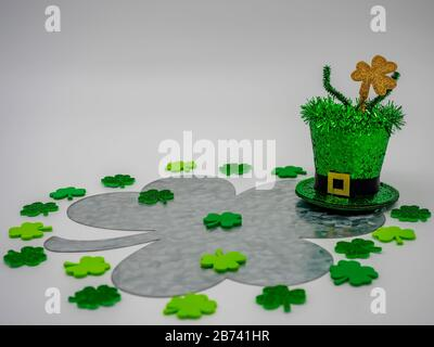 Leprechaun hat with a on top of a large rustic metal four leaf clover with lots of smaller green four leaf clovers decorating it for St. Patrick's Day - Stock Photo